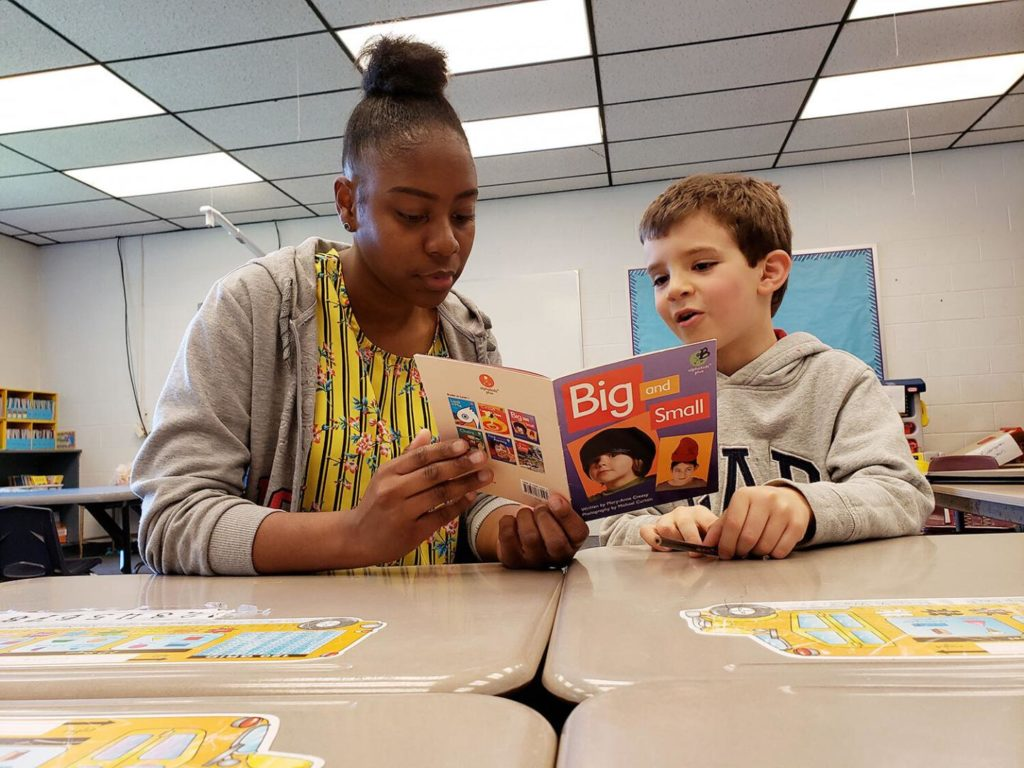 Carol helps 6-year-old native Spanish speaker Bernat Gasch read a book in English.