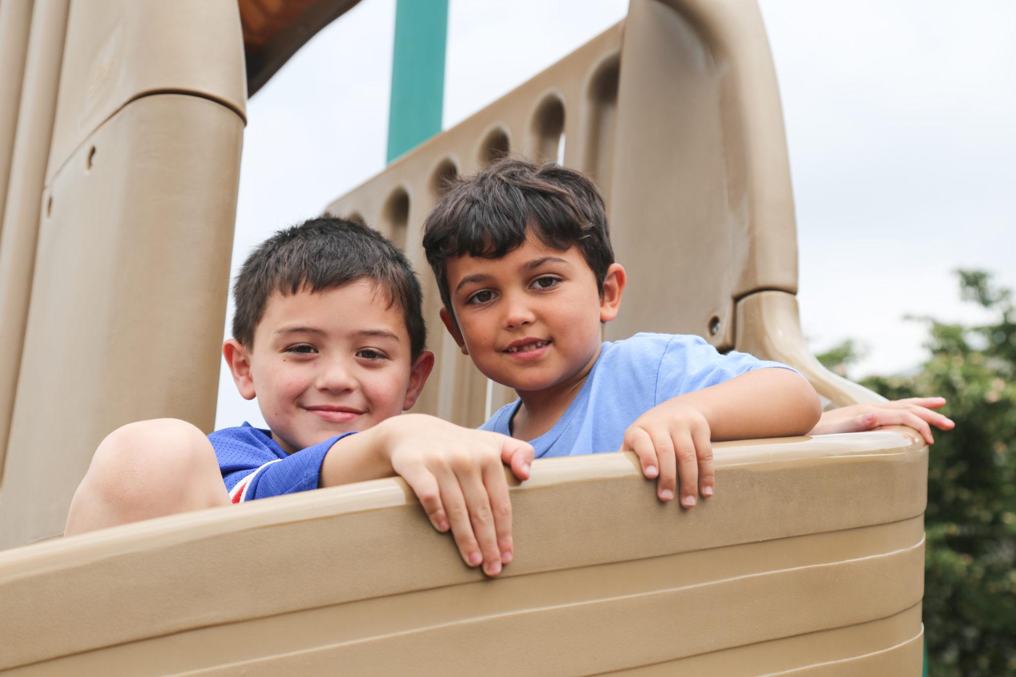 students sitting on slide smiling