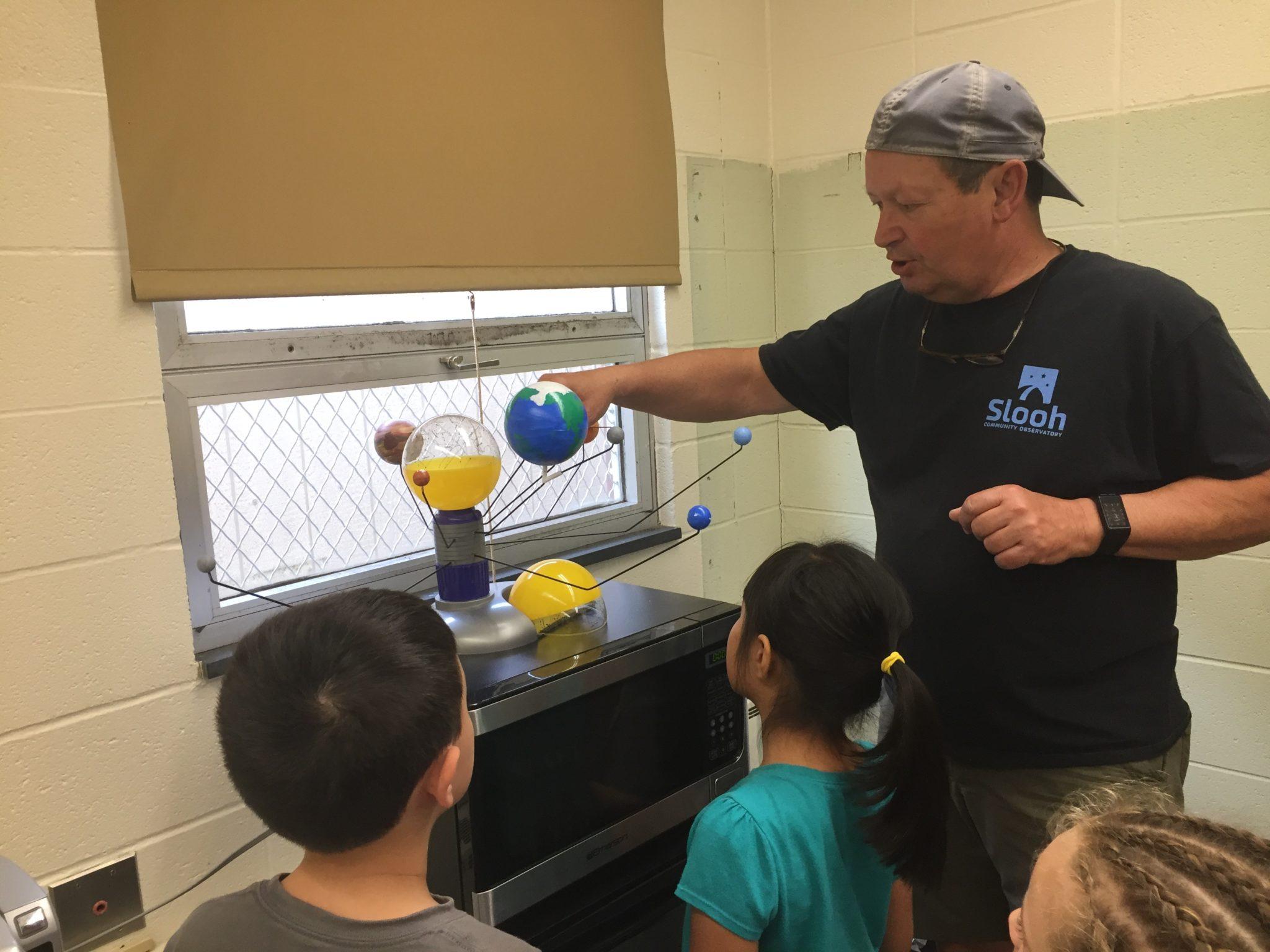 Students gathered around solar system module