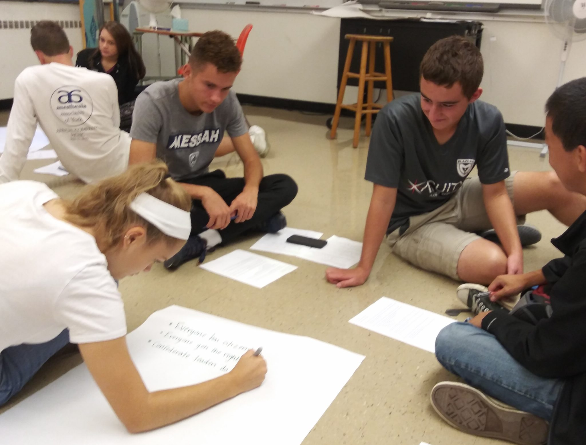 Students collaborating on a class project, drawing on paper on the floor