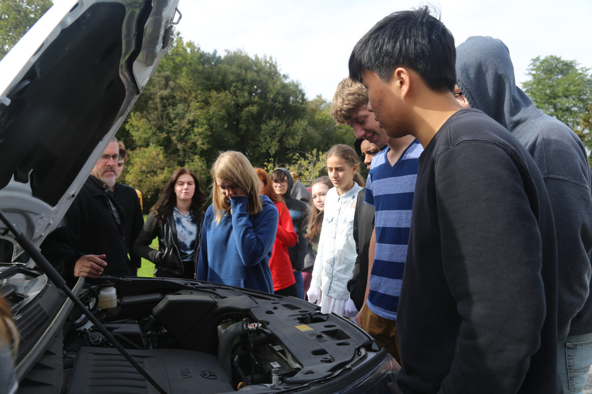 Students inspecting engine of a car