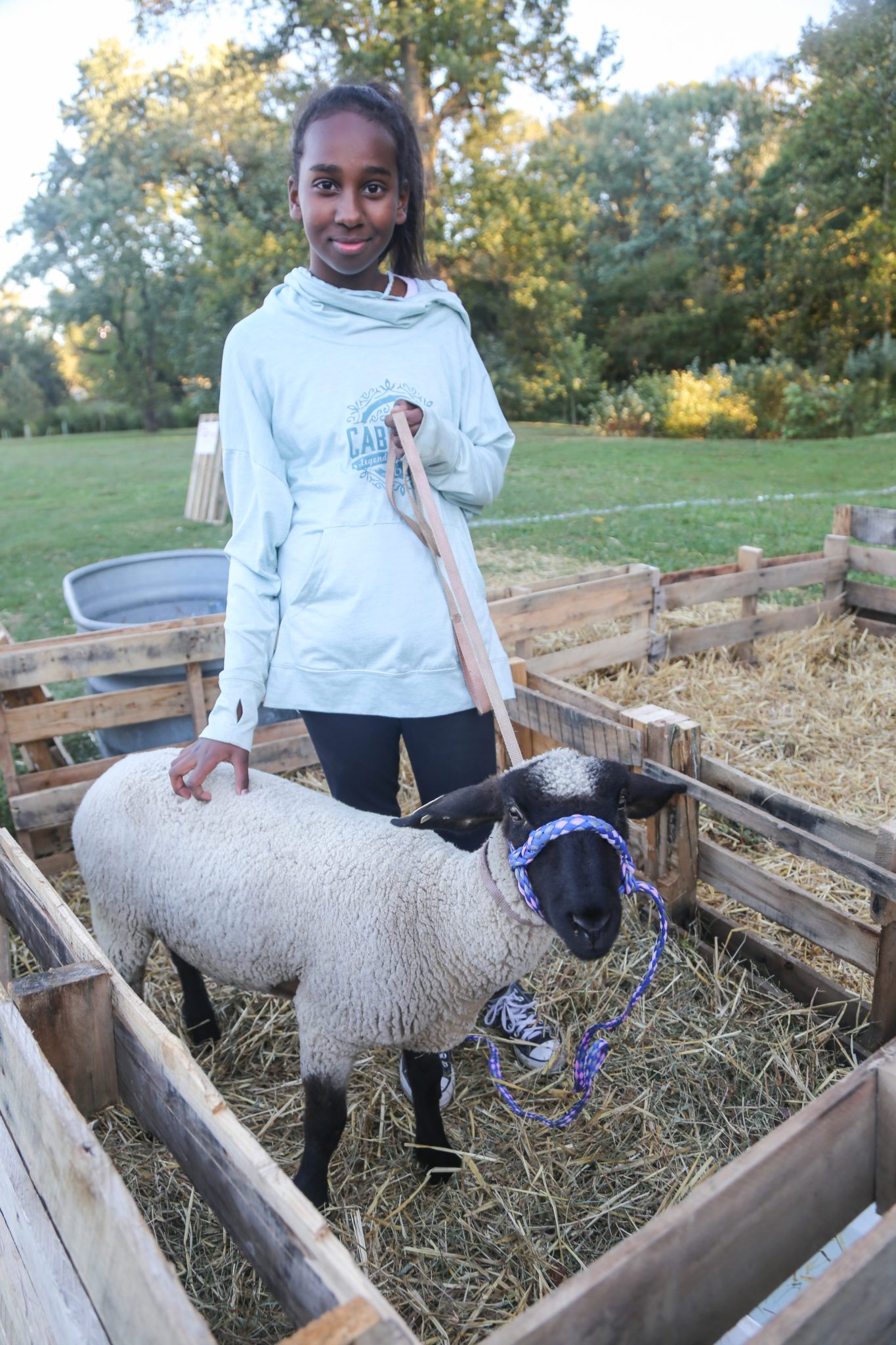 student with lamb at petting zoo during homecoming 2019