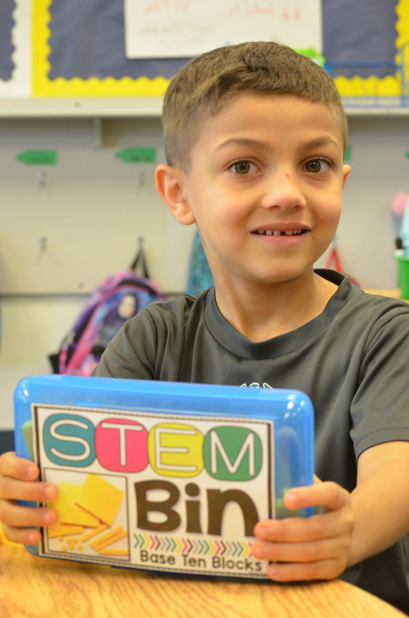 student holding stem bin