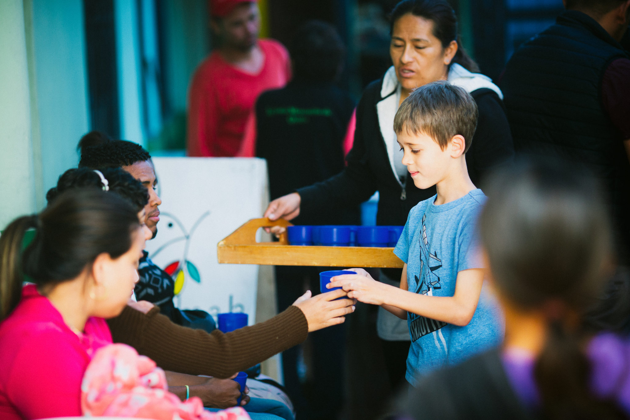 students handing out blue cups to people