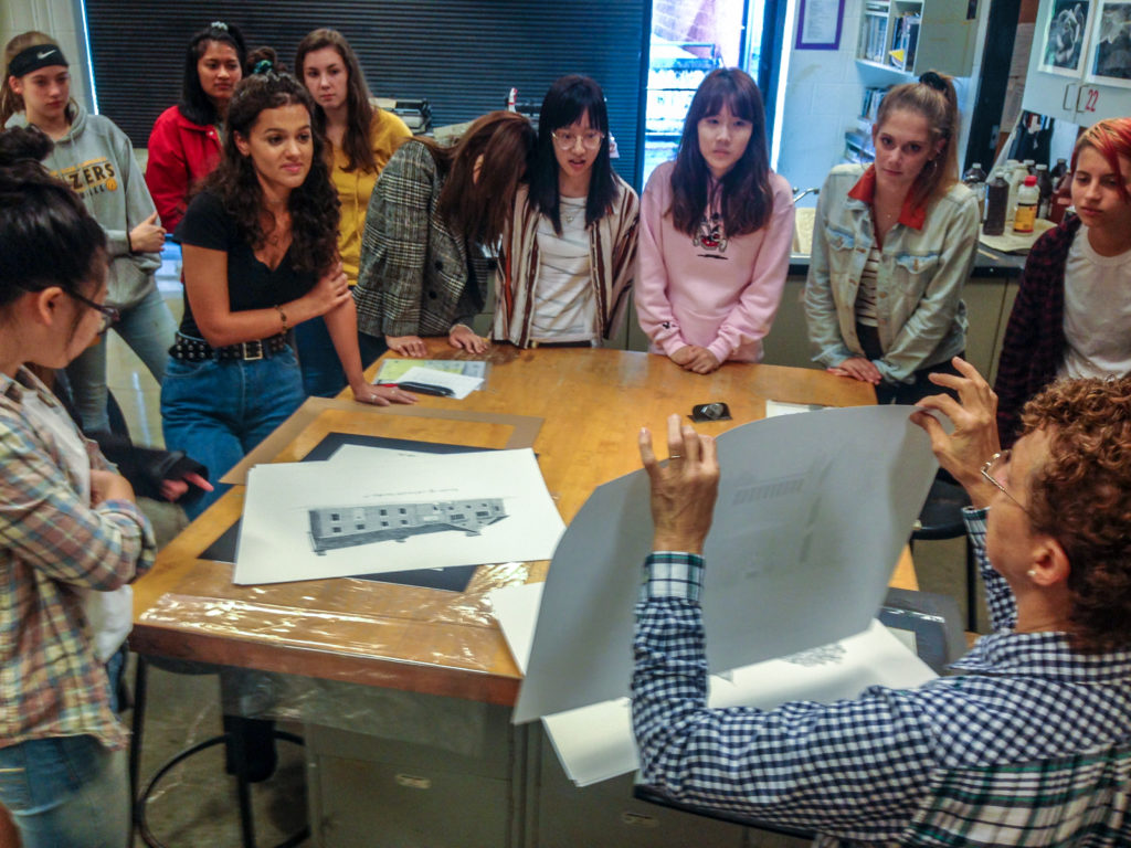 Students standing around table looking at blue prints
