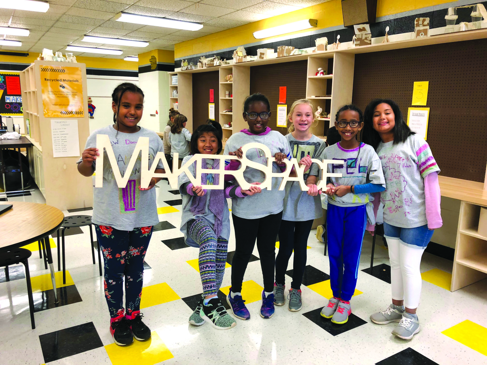 students holding makerspace banner