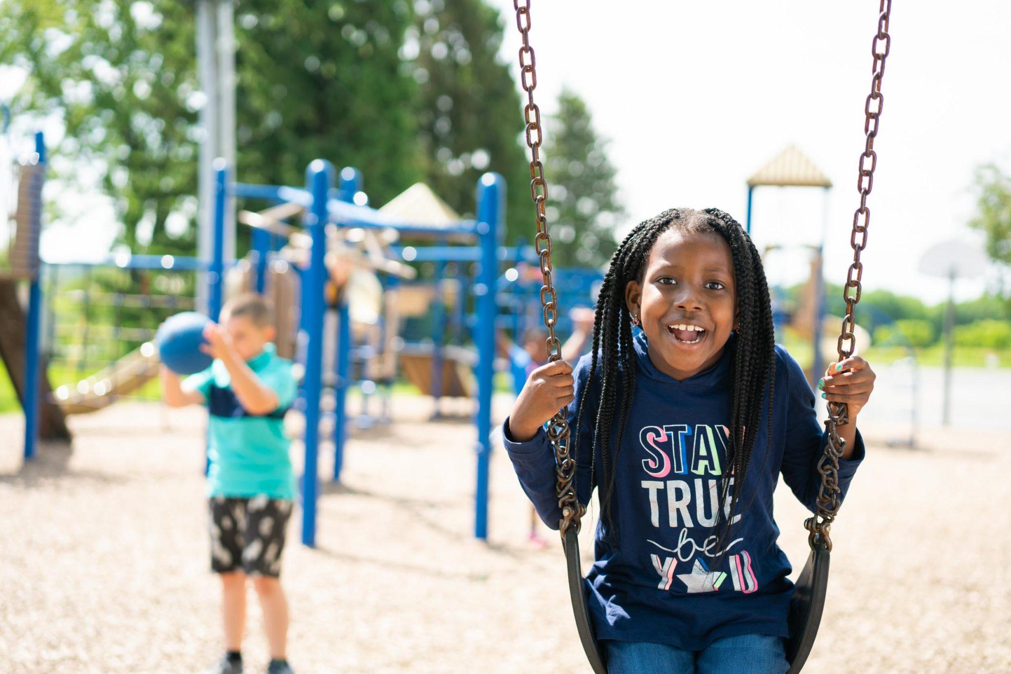 student on playground swings