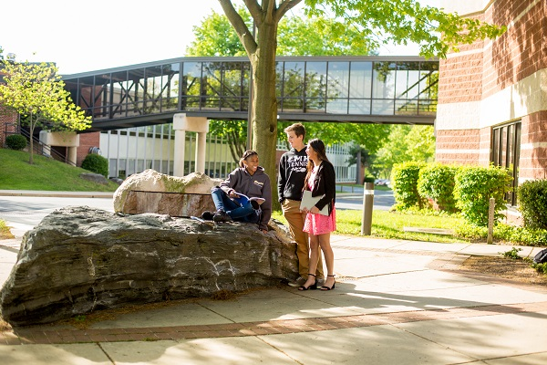 students sitting on rock