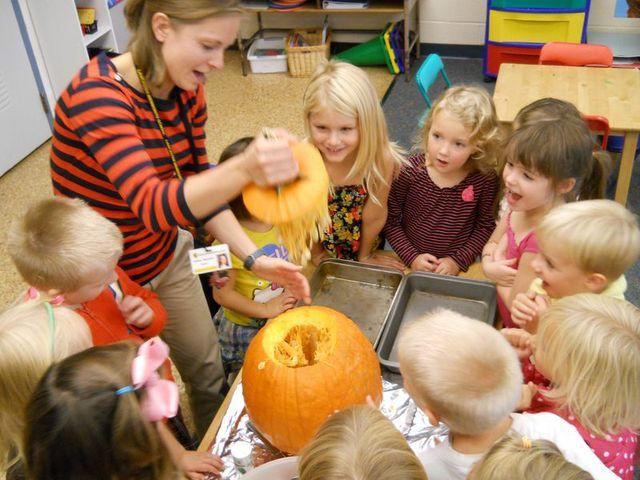 students carving a pumpkin