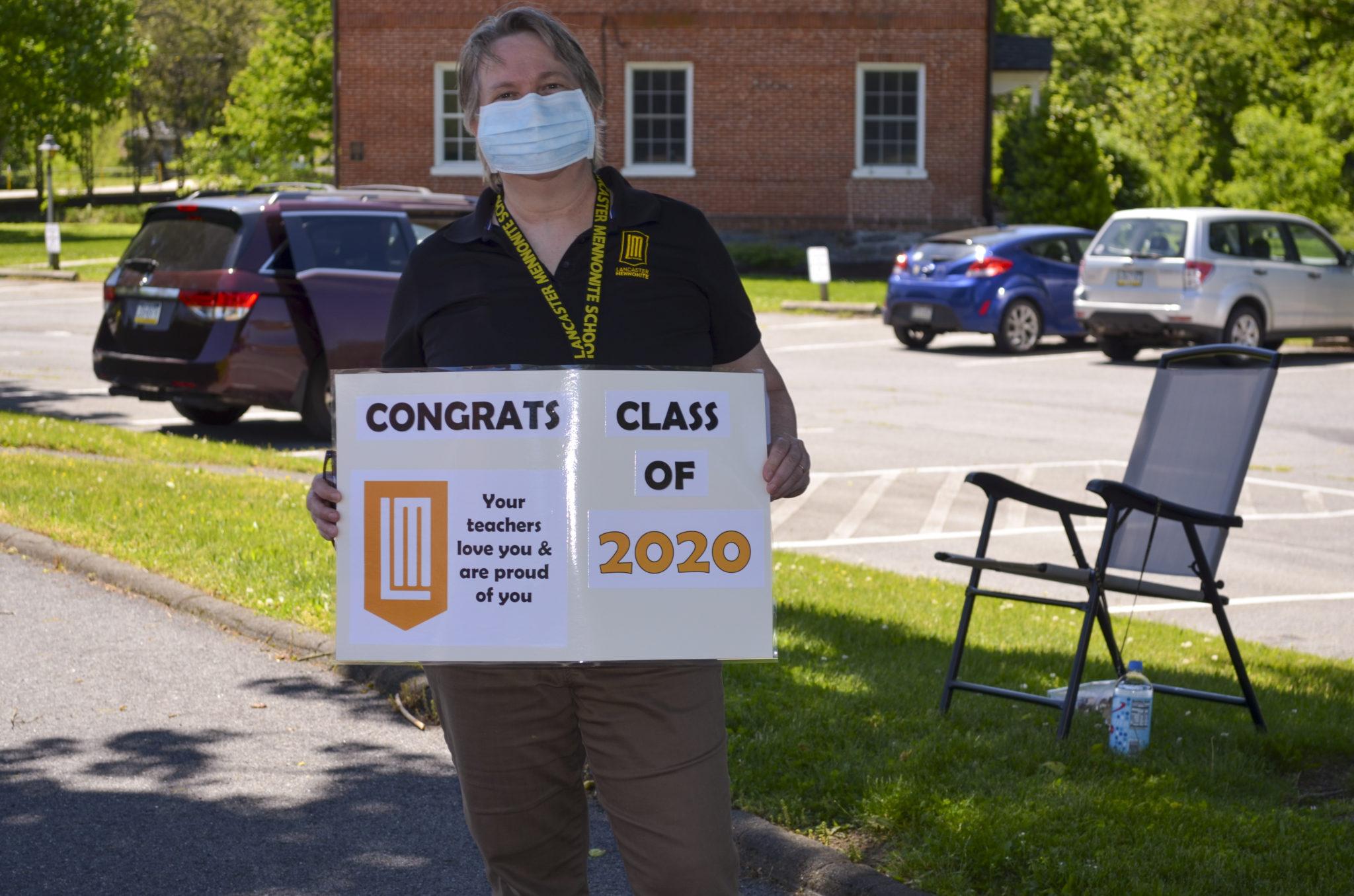 teacher holding congratulation sign for graduates
