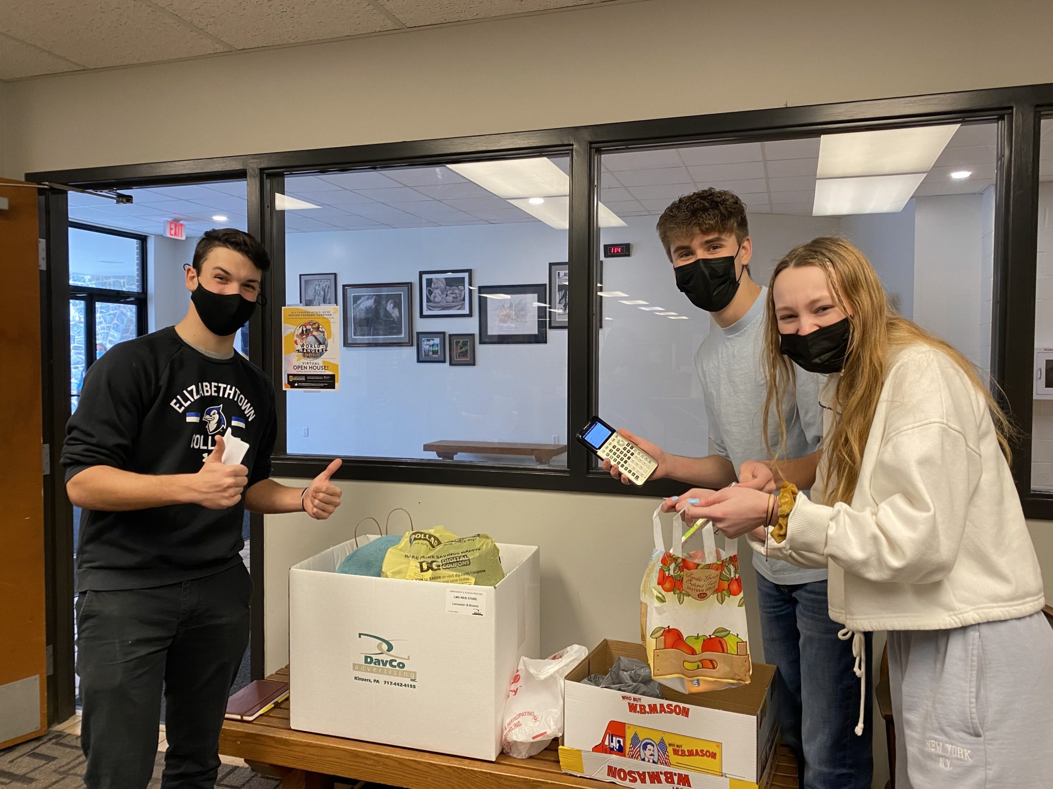 students holding canned goods