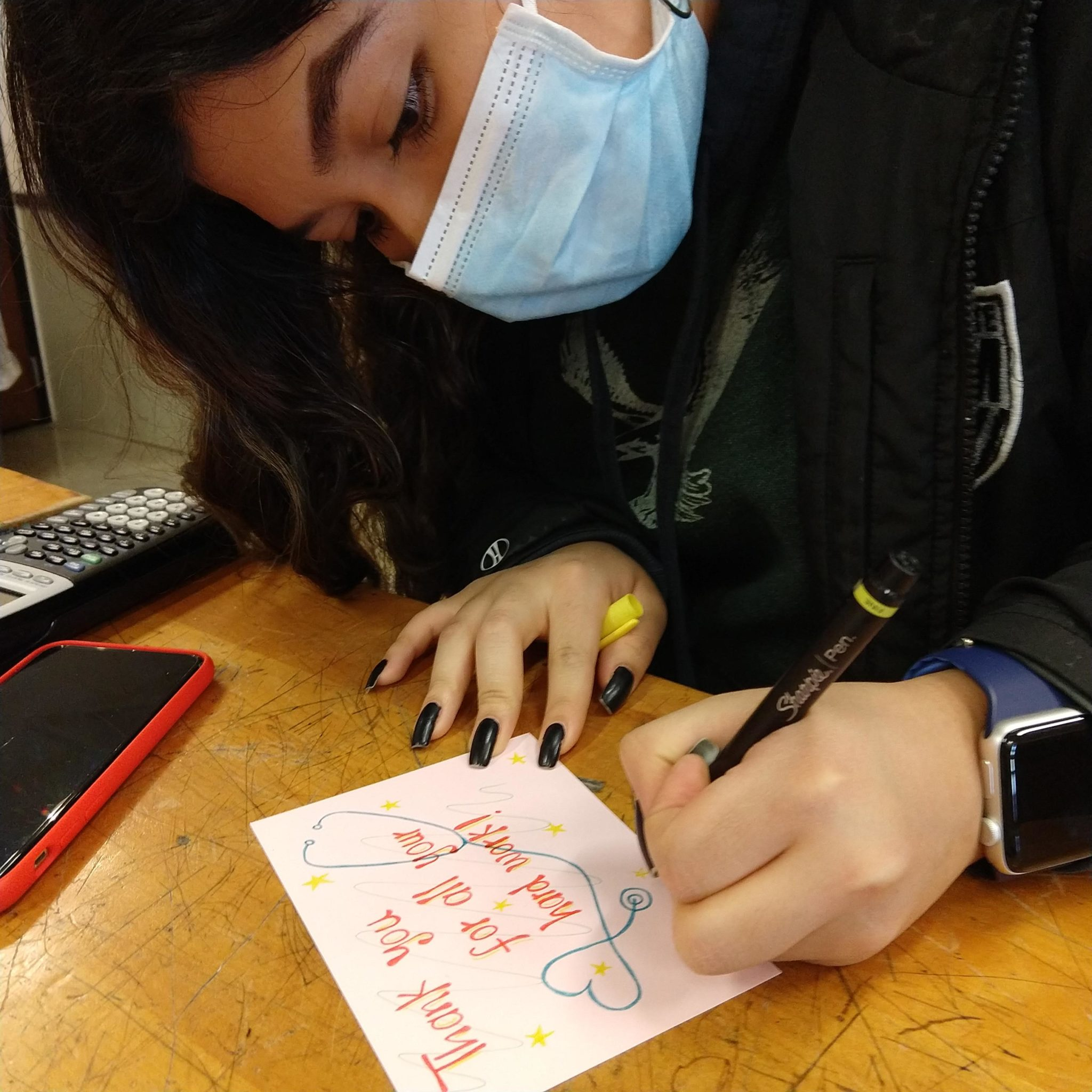 student hand writing card