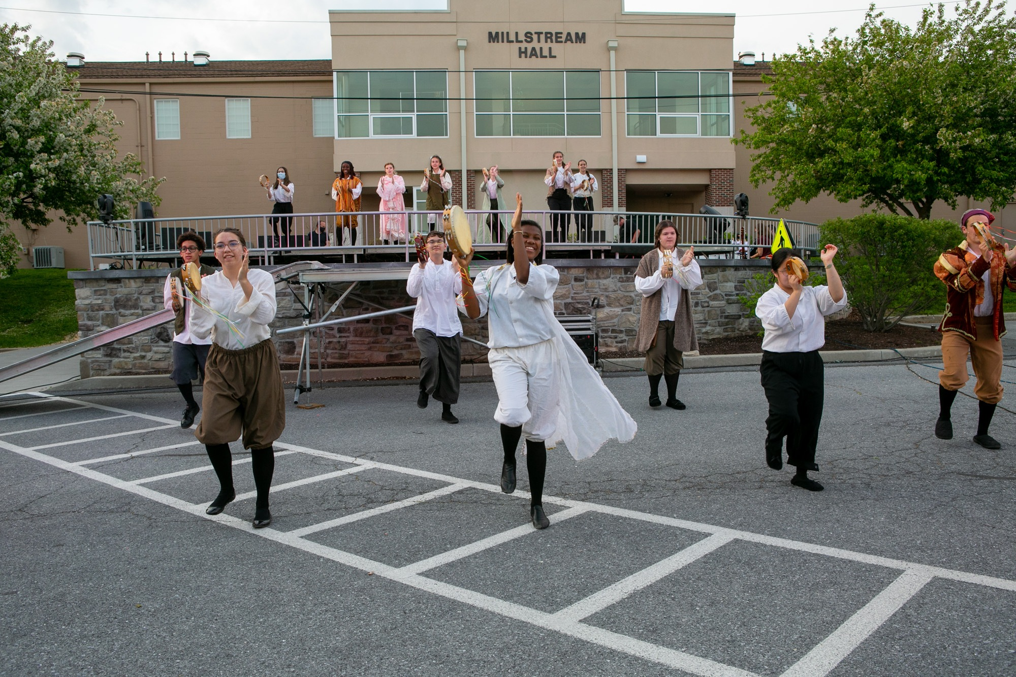 spring drama students dancing and singing outdoors