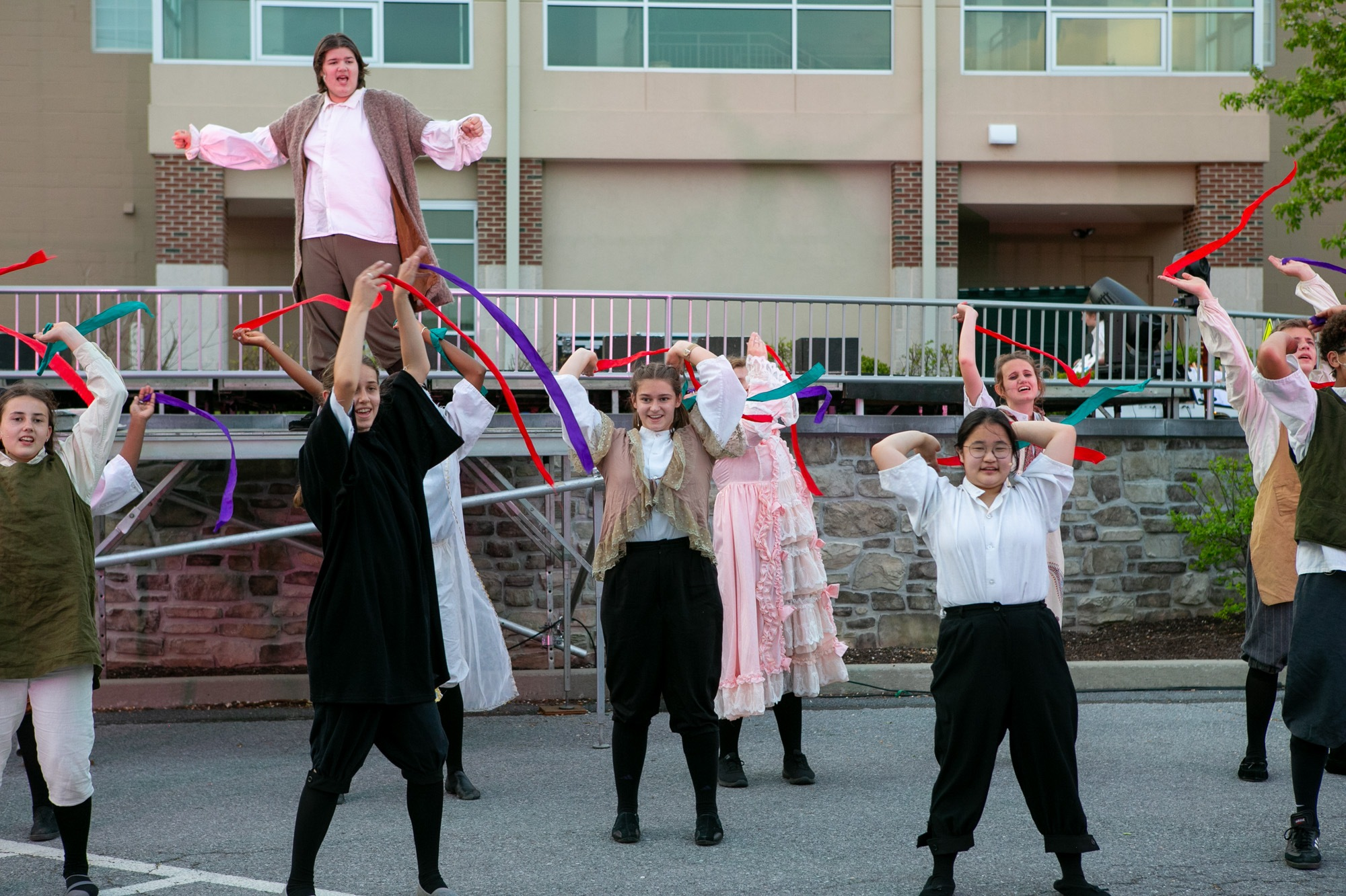 students dancing and acting during the performance of all the worlds a stage