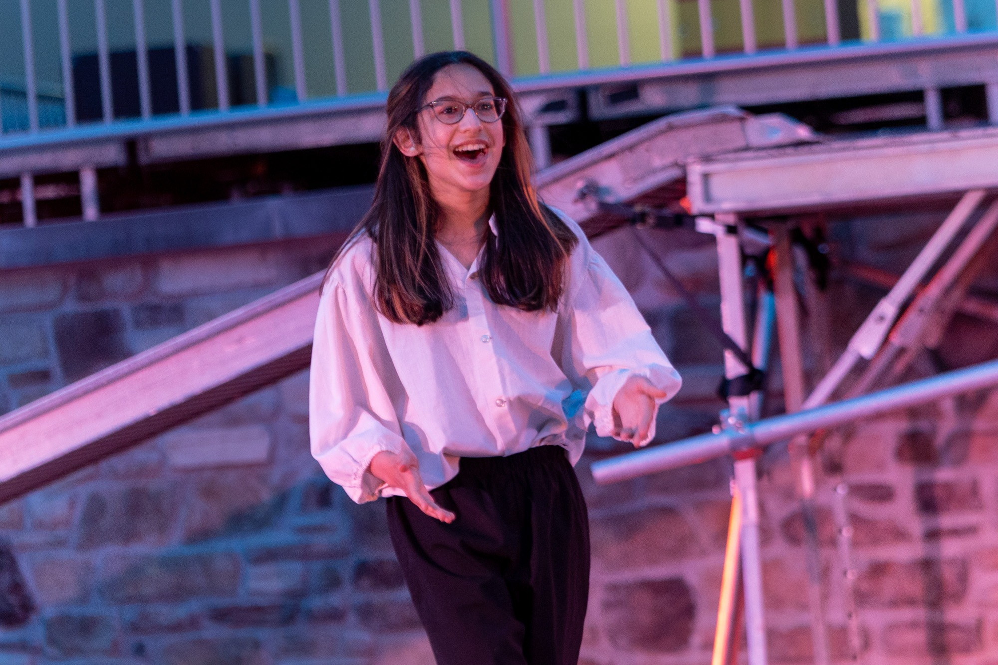 student smiling during the performance of all the worlds a stage
