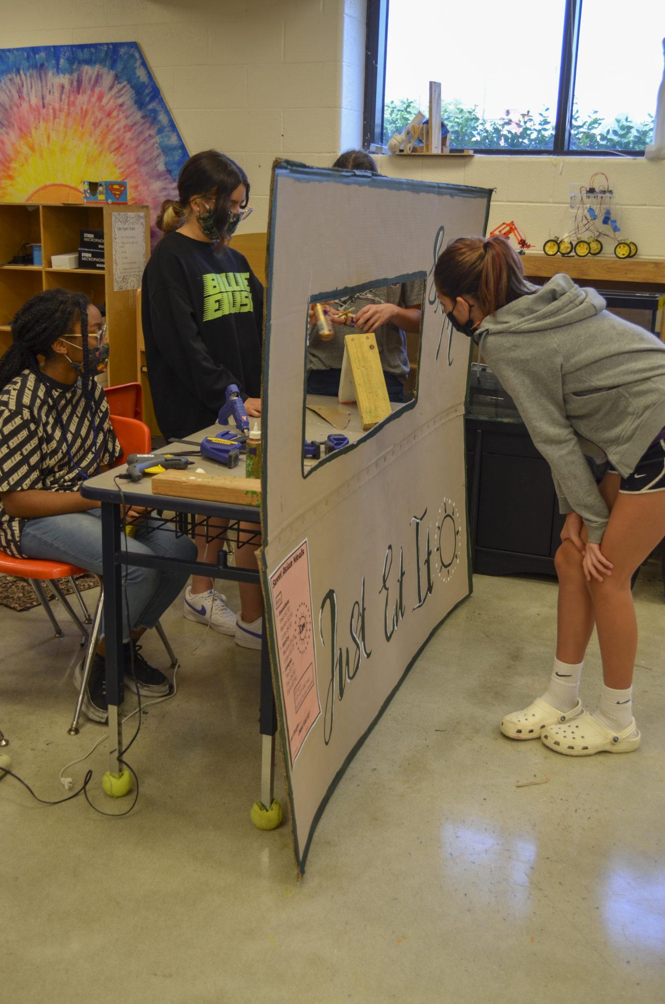 students examining work at set up booth