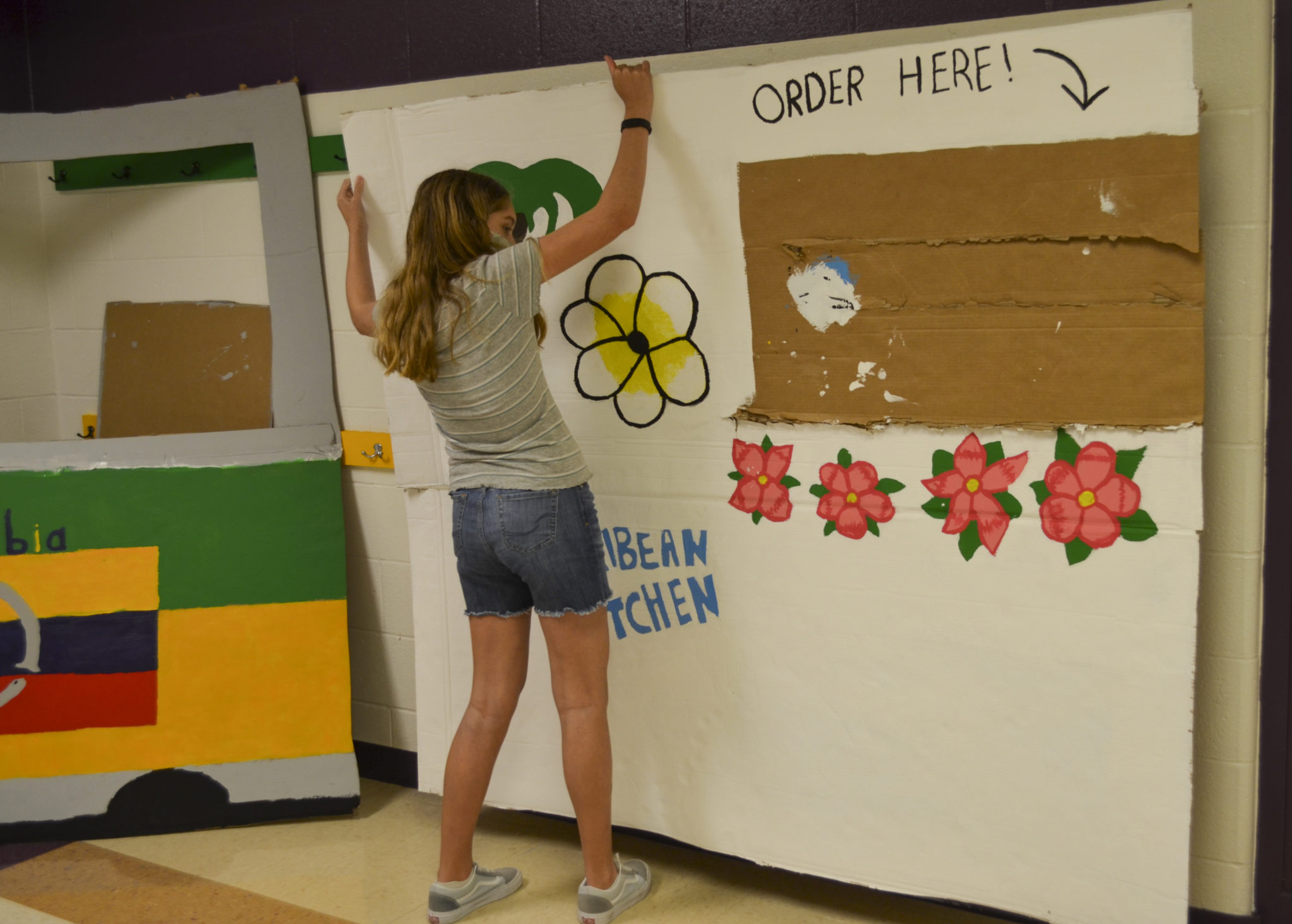 student hanging banner for caribbean kitchen project