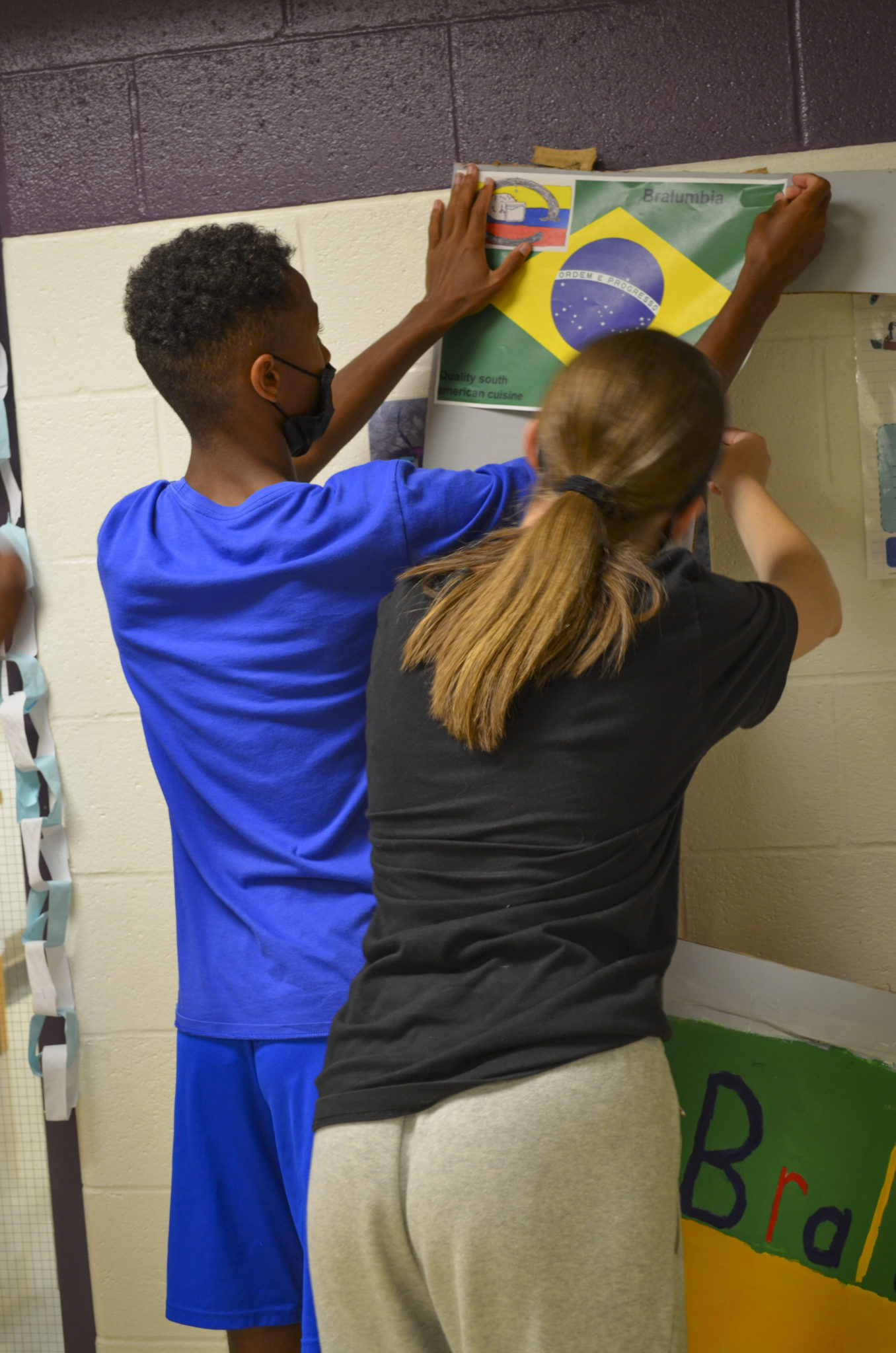 students hanging current projects on wall