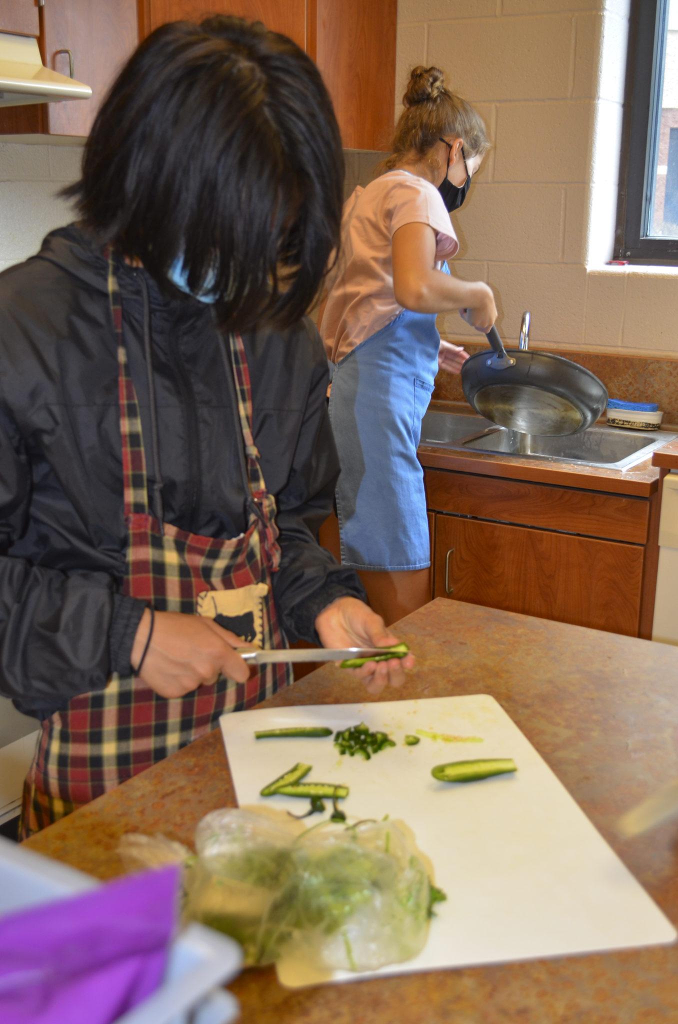 student cutting squash in homec class