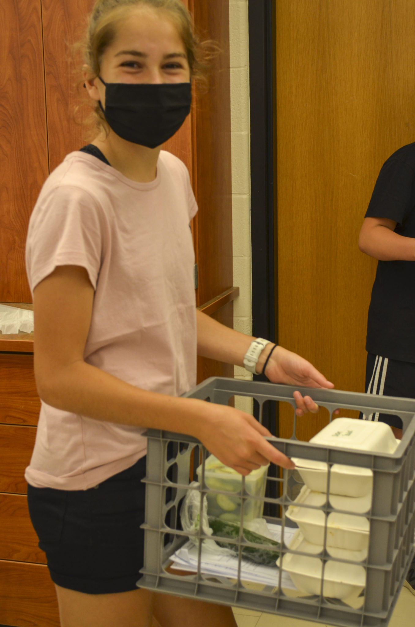 student carrying eggs in milk carton crate