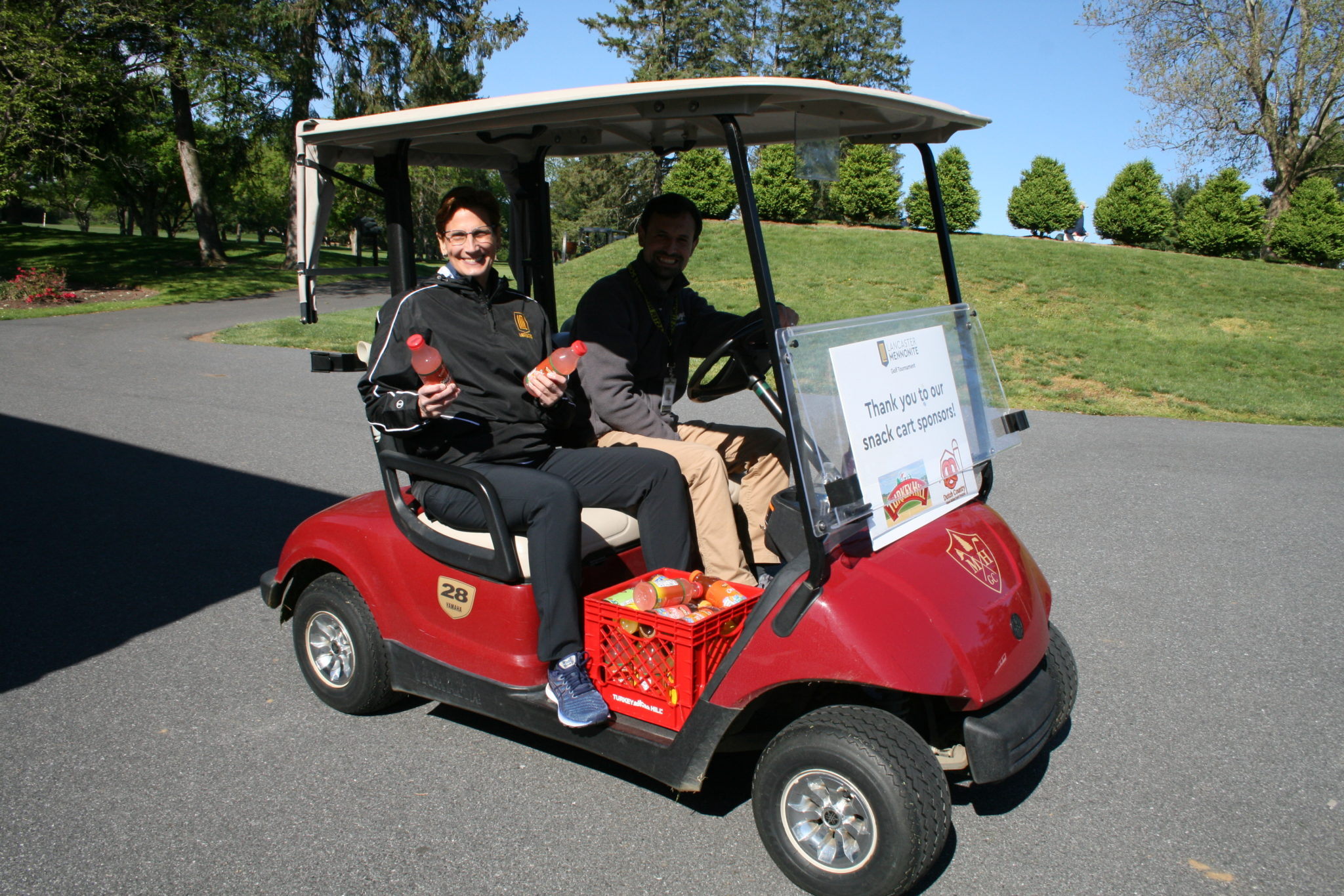 Dr. T & jon heinly handing out refreshments at the golf tournament