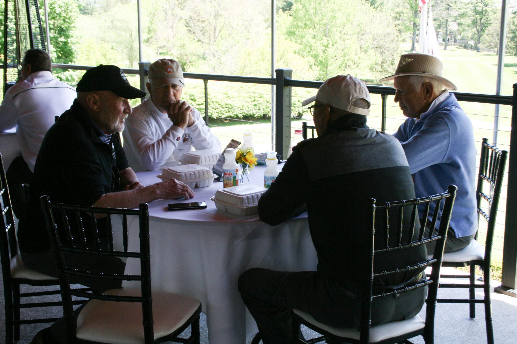 4 men talking around round table
