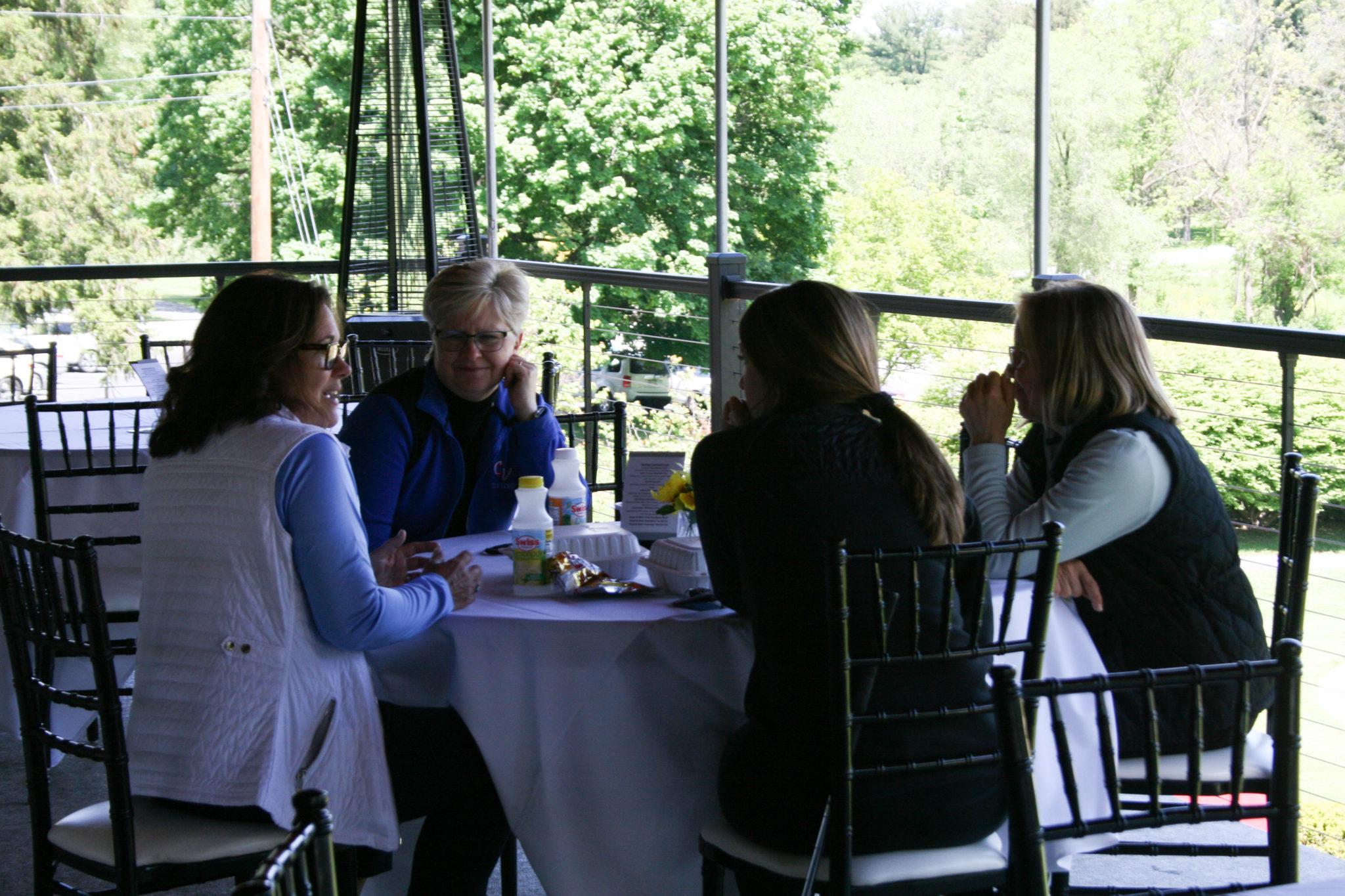 4 women talking around table