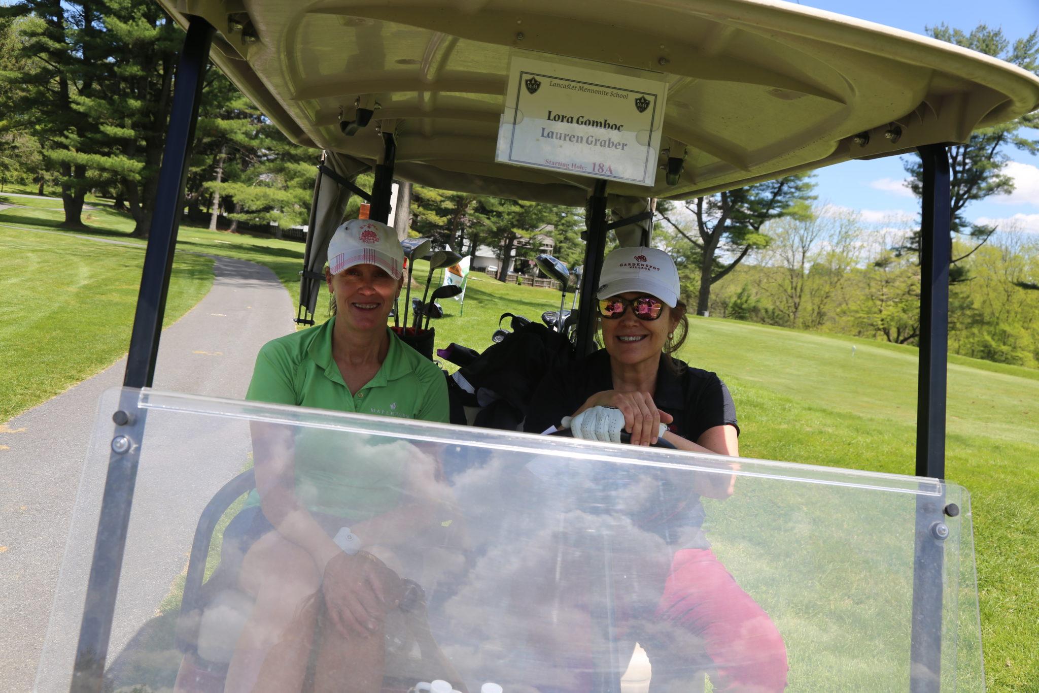 2 women on golf cart