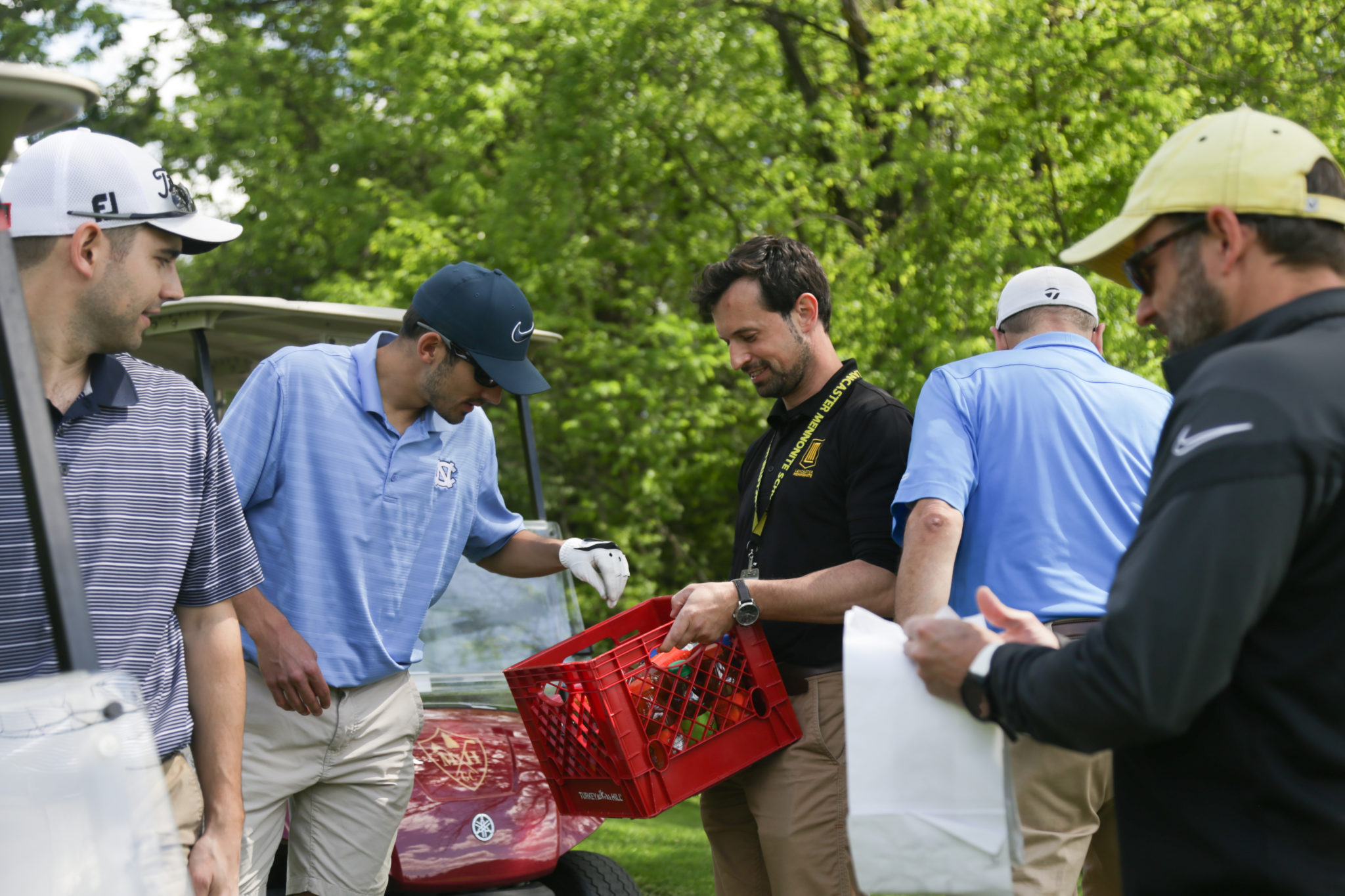 jon heinly handing out drinks at LM golf tournament