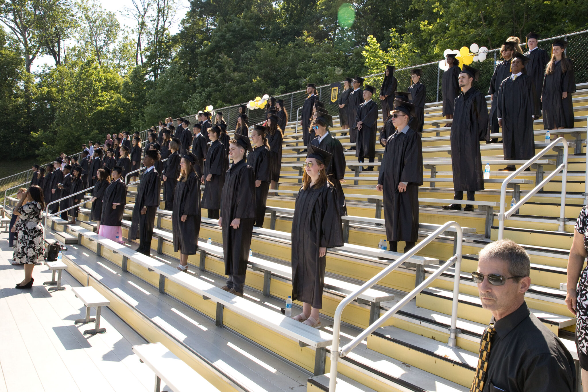 graduates sitting in bleachers during commencement service