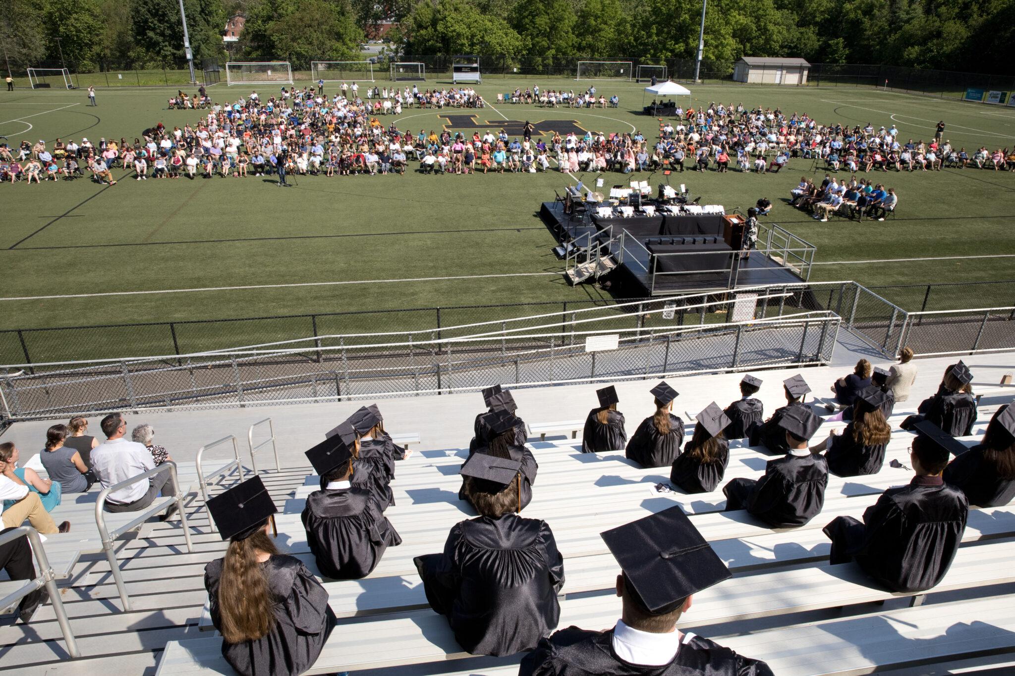 graduation service from bleachers into turf field view