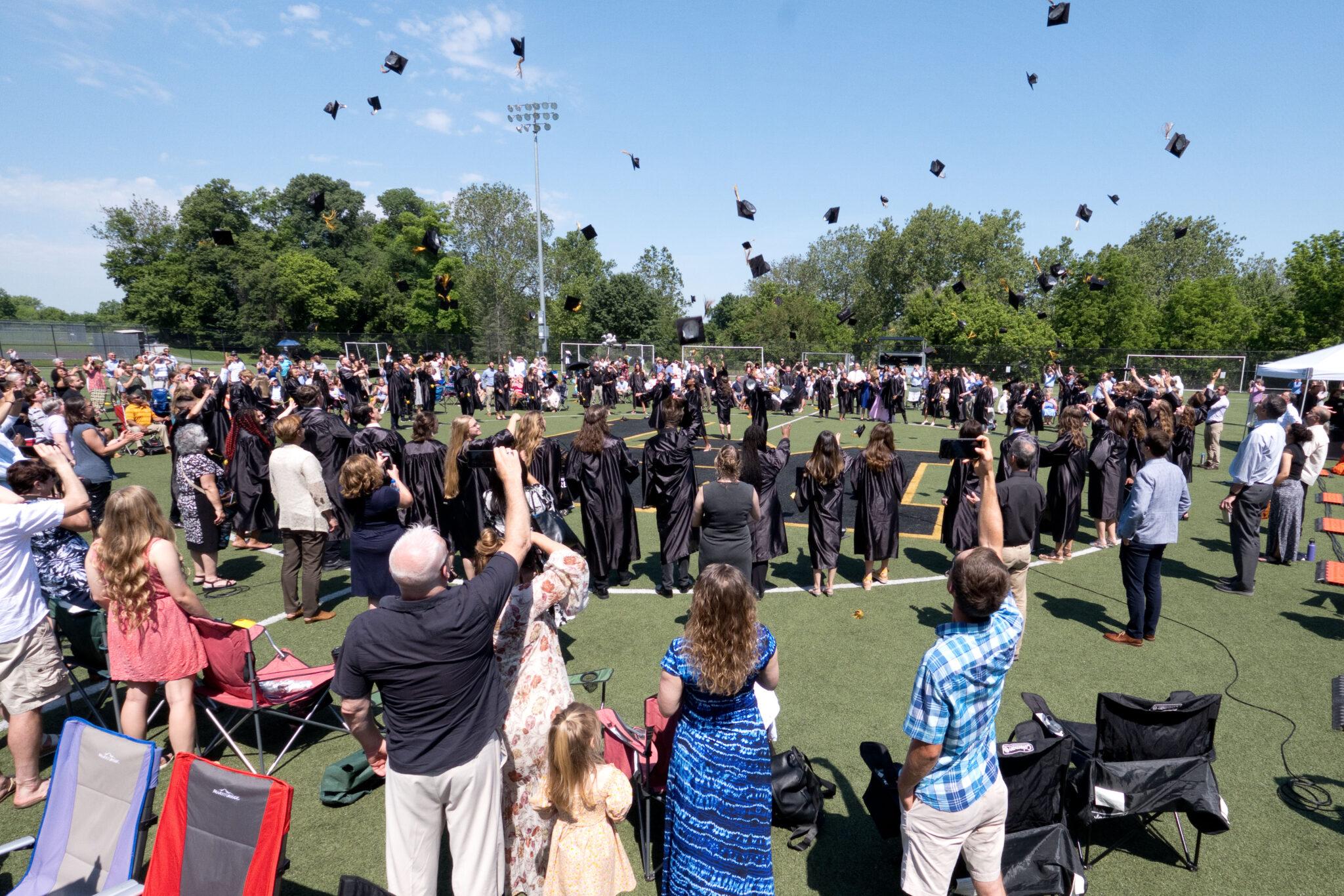 graduates throwing caps commencement