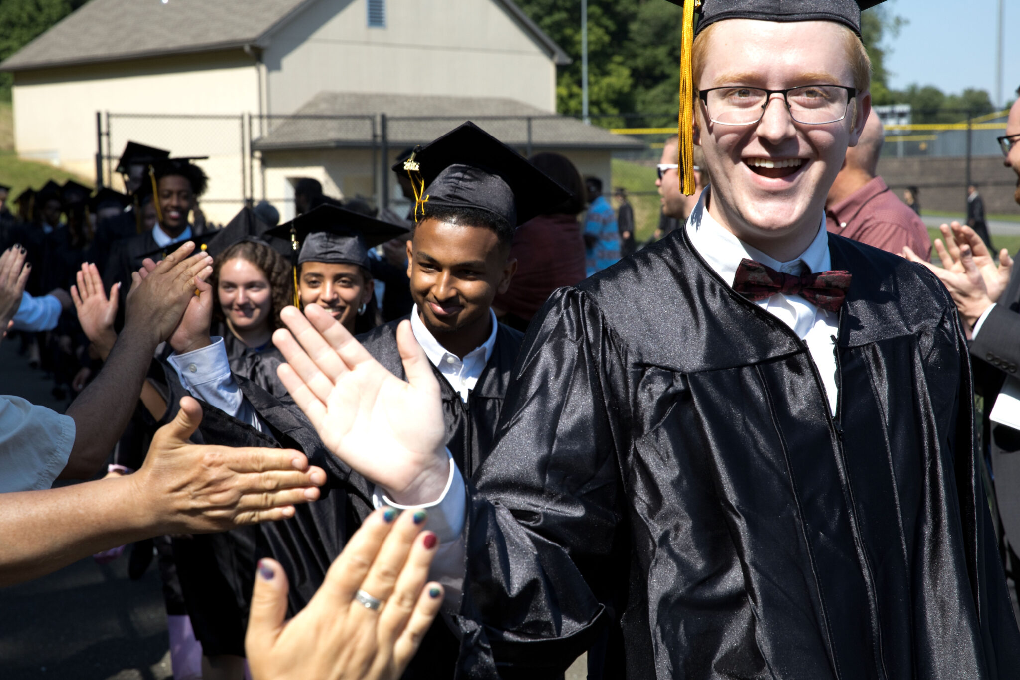graduates walking into commencement high fiving teachers