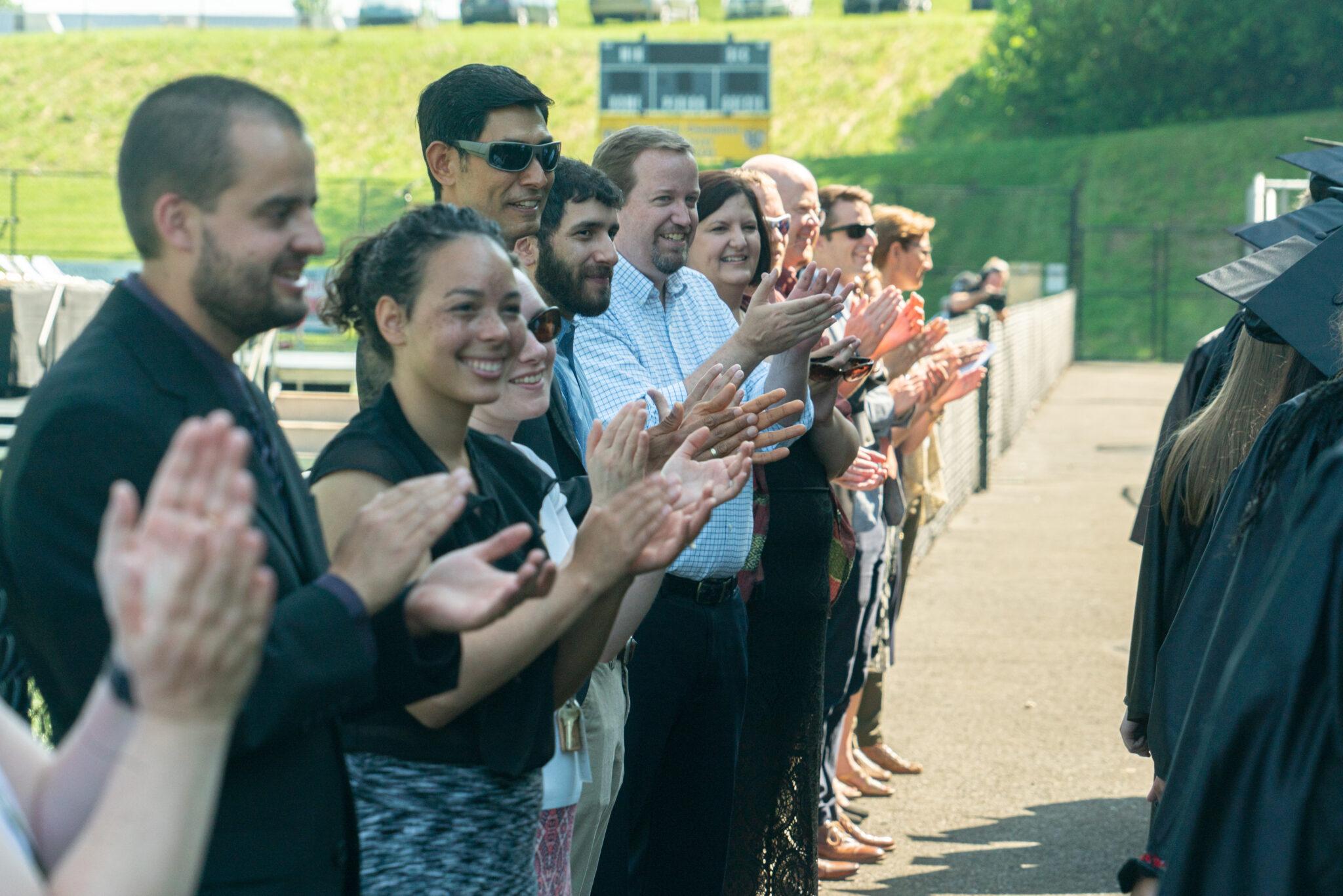 teachers cheering on graduates walking into commencement