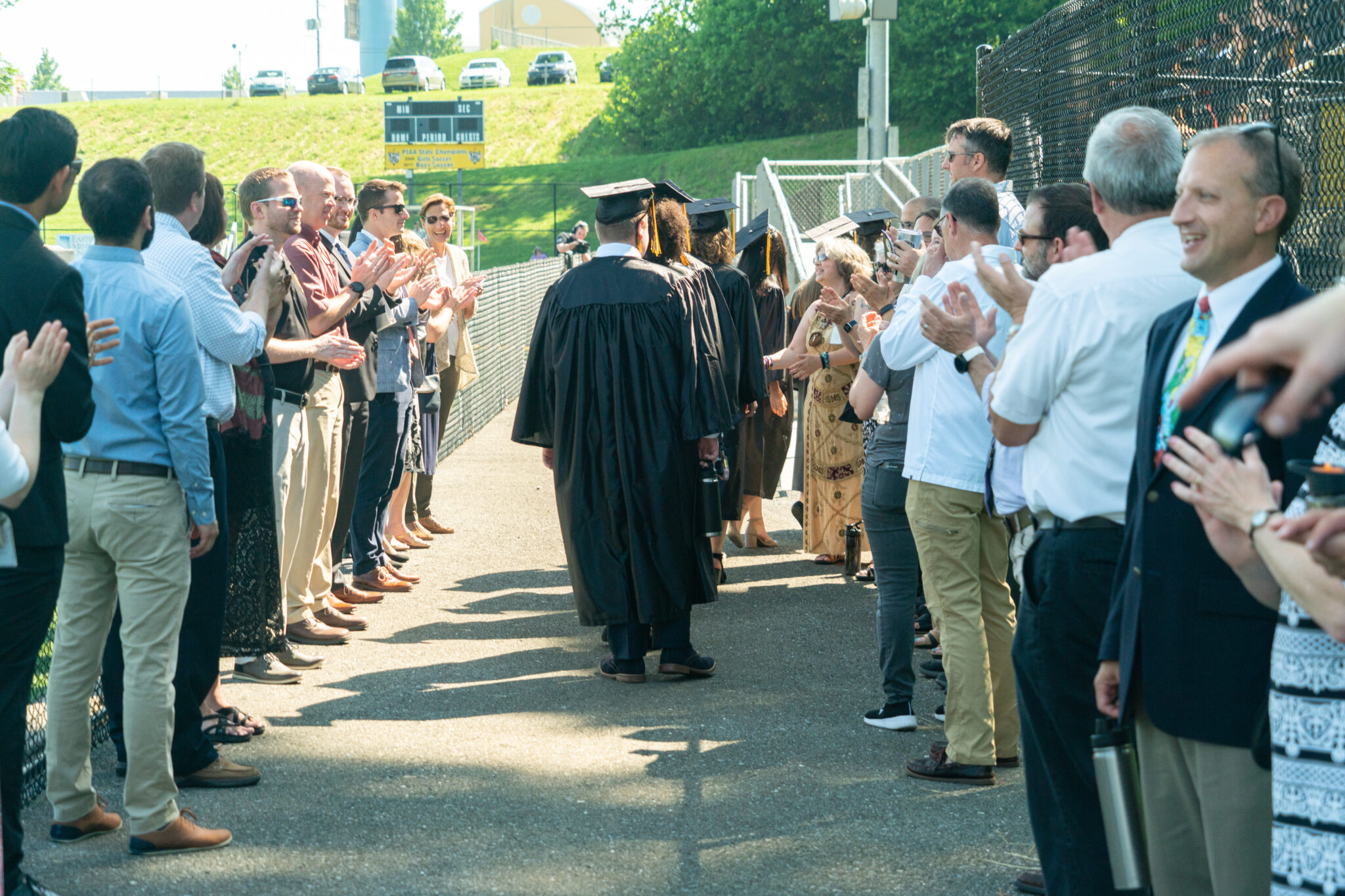 graduates walking into commencement in tunnel of teachers