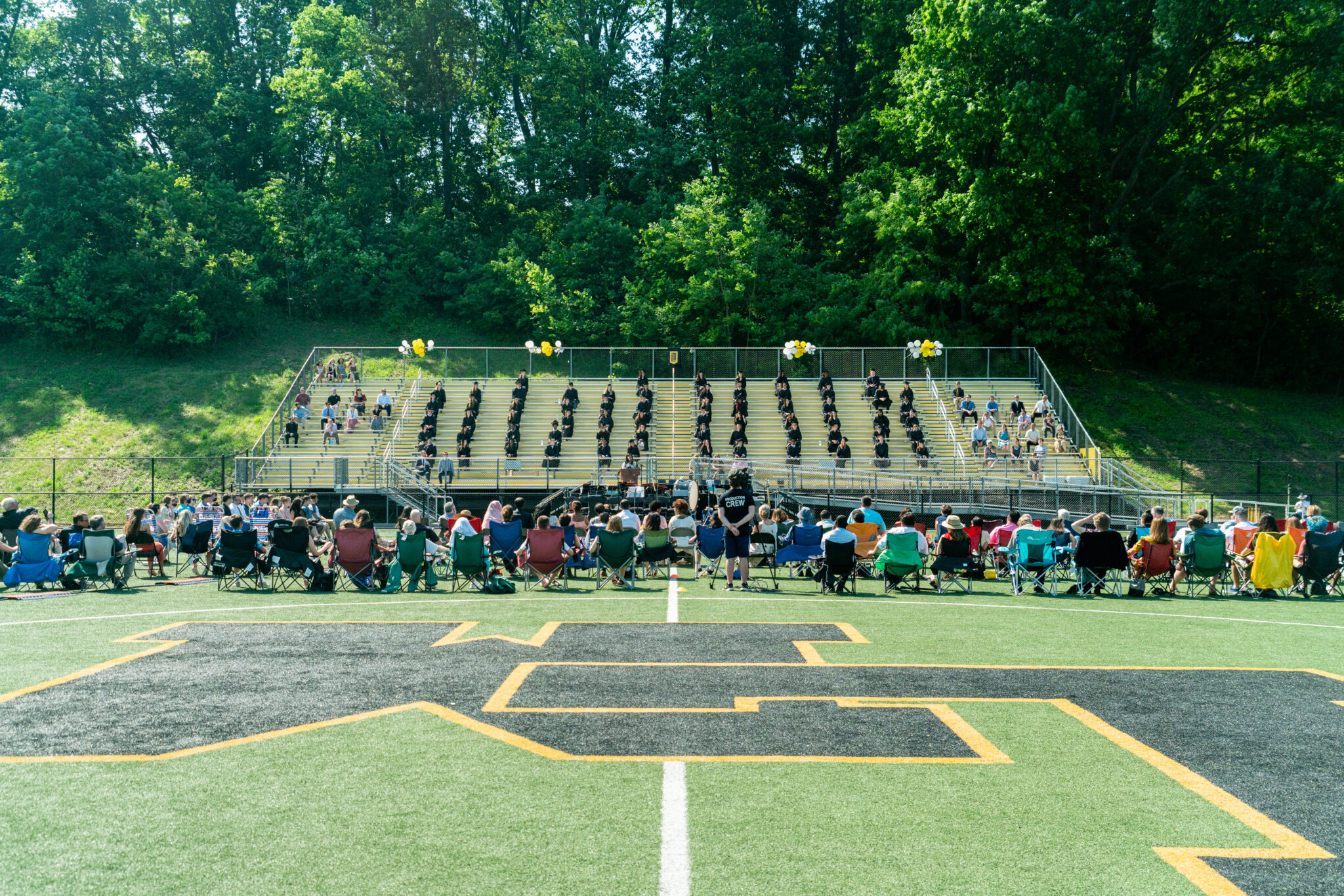 wide angle look at graduation on turf field with bleachers in back