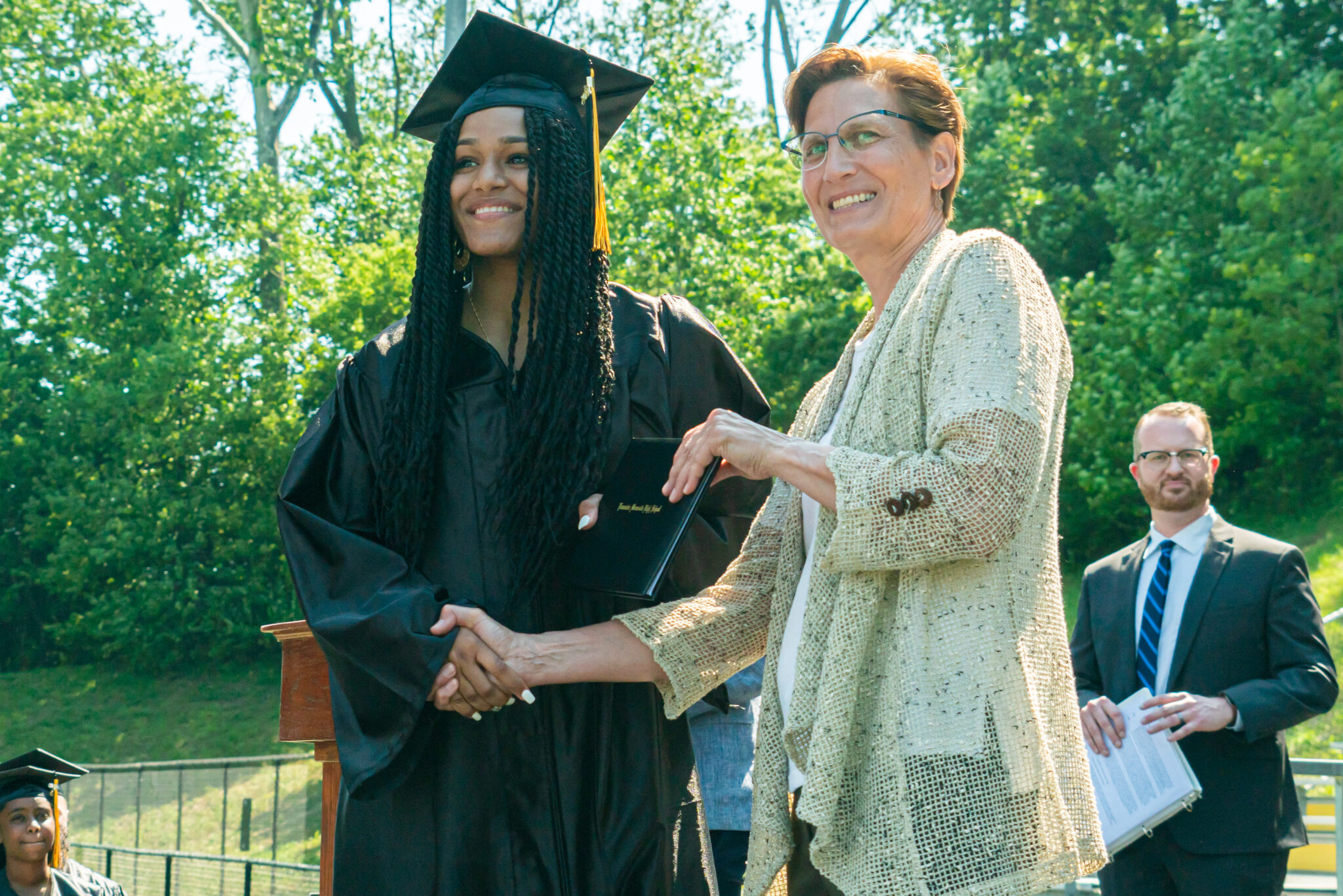 Superintendent gives diploma and shakes hand of student graduate