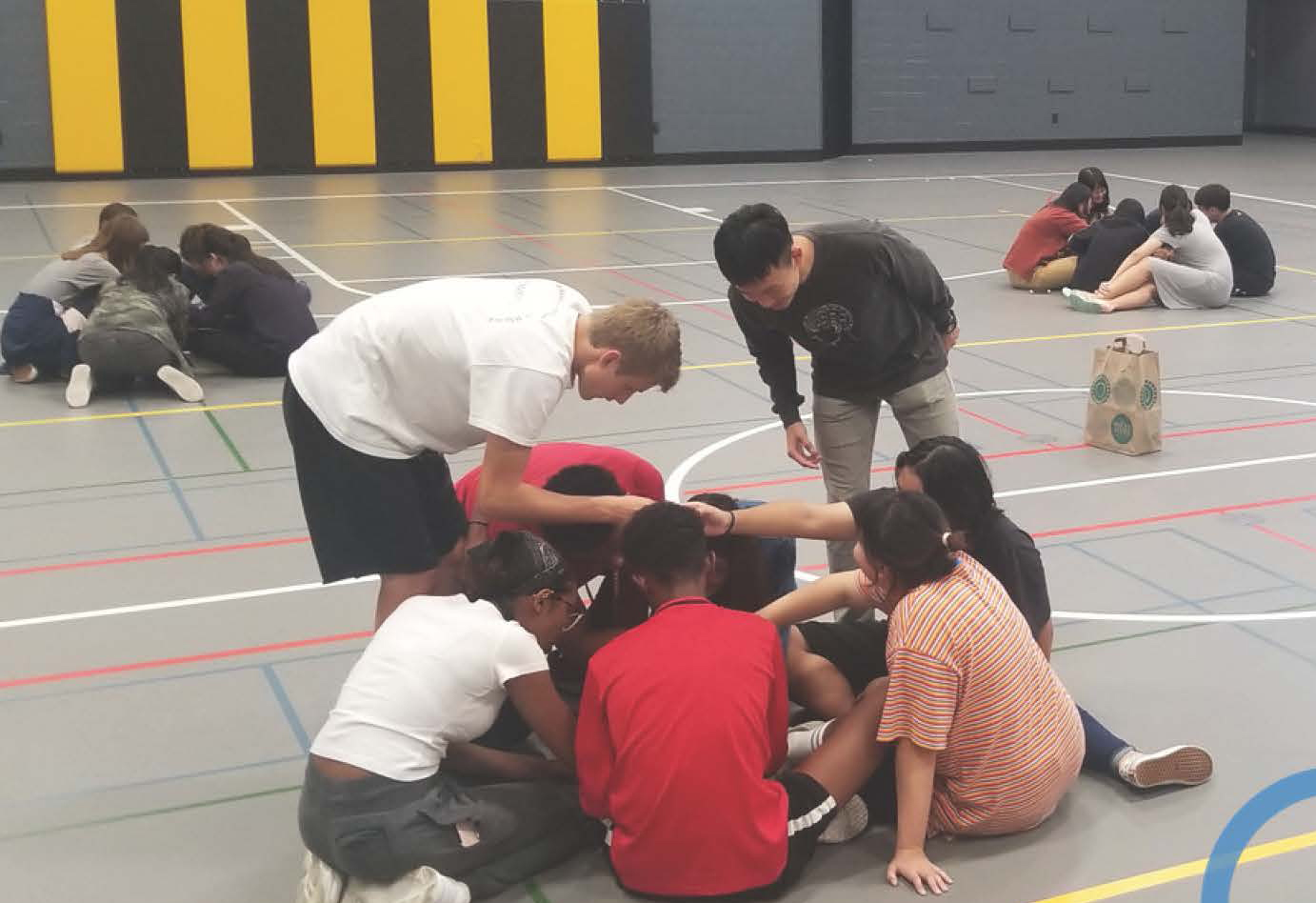 students in the gym doing an activity sitting in a circle