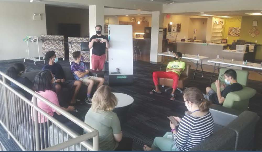 residence hall students in lounge listening