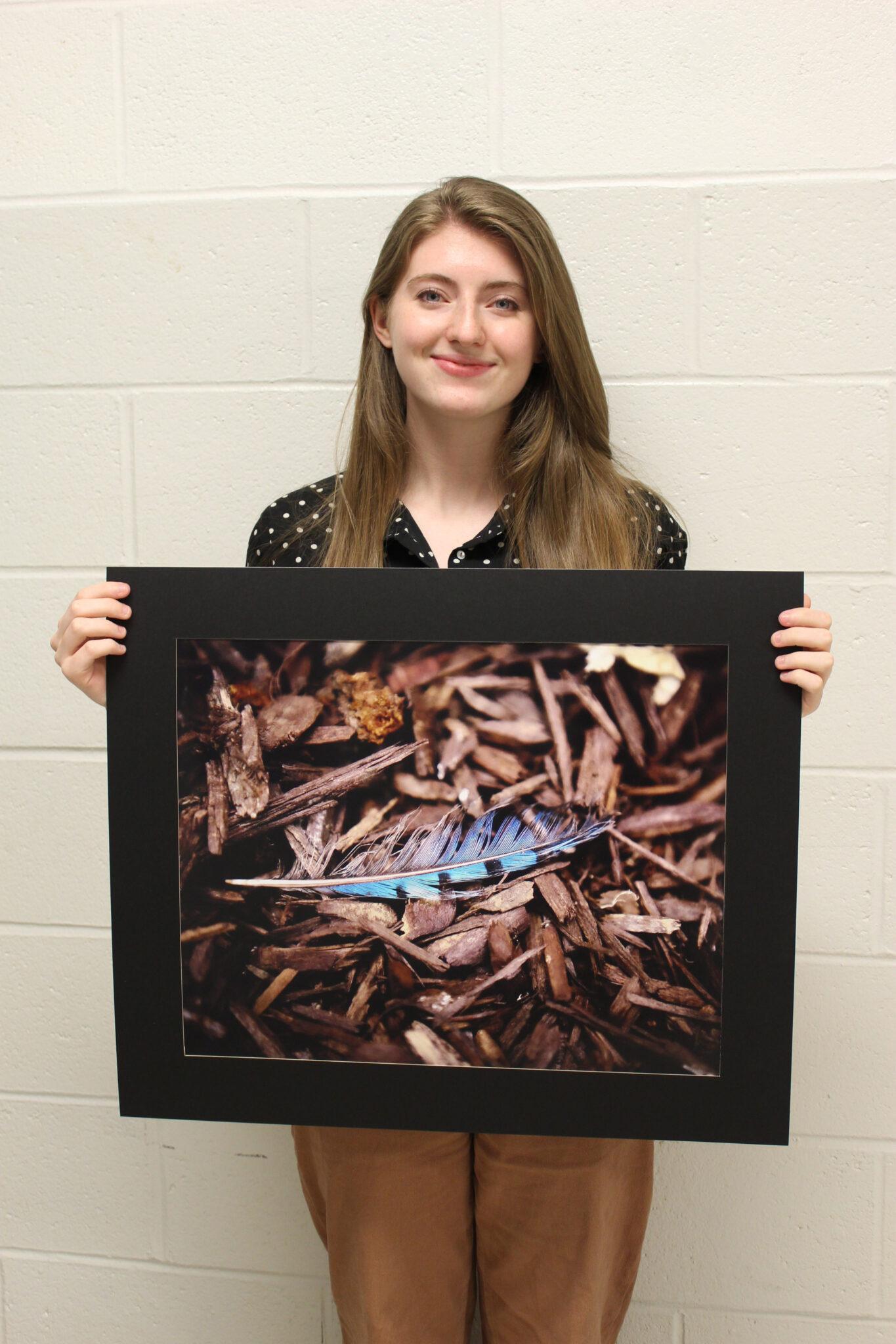 Photo of student holding artwork