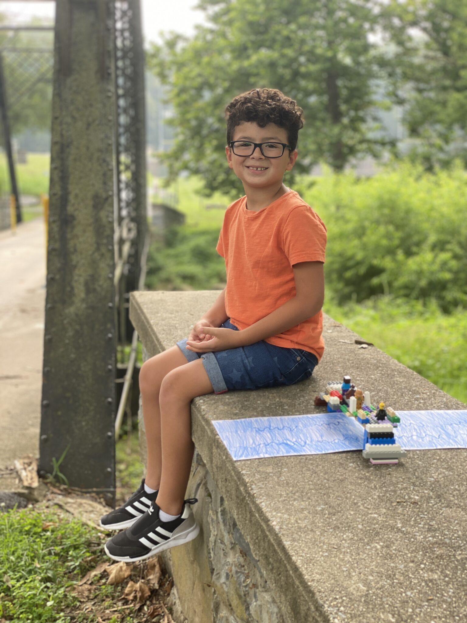 student on bridge with lego bridge creation