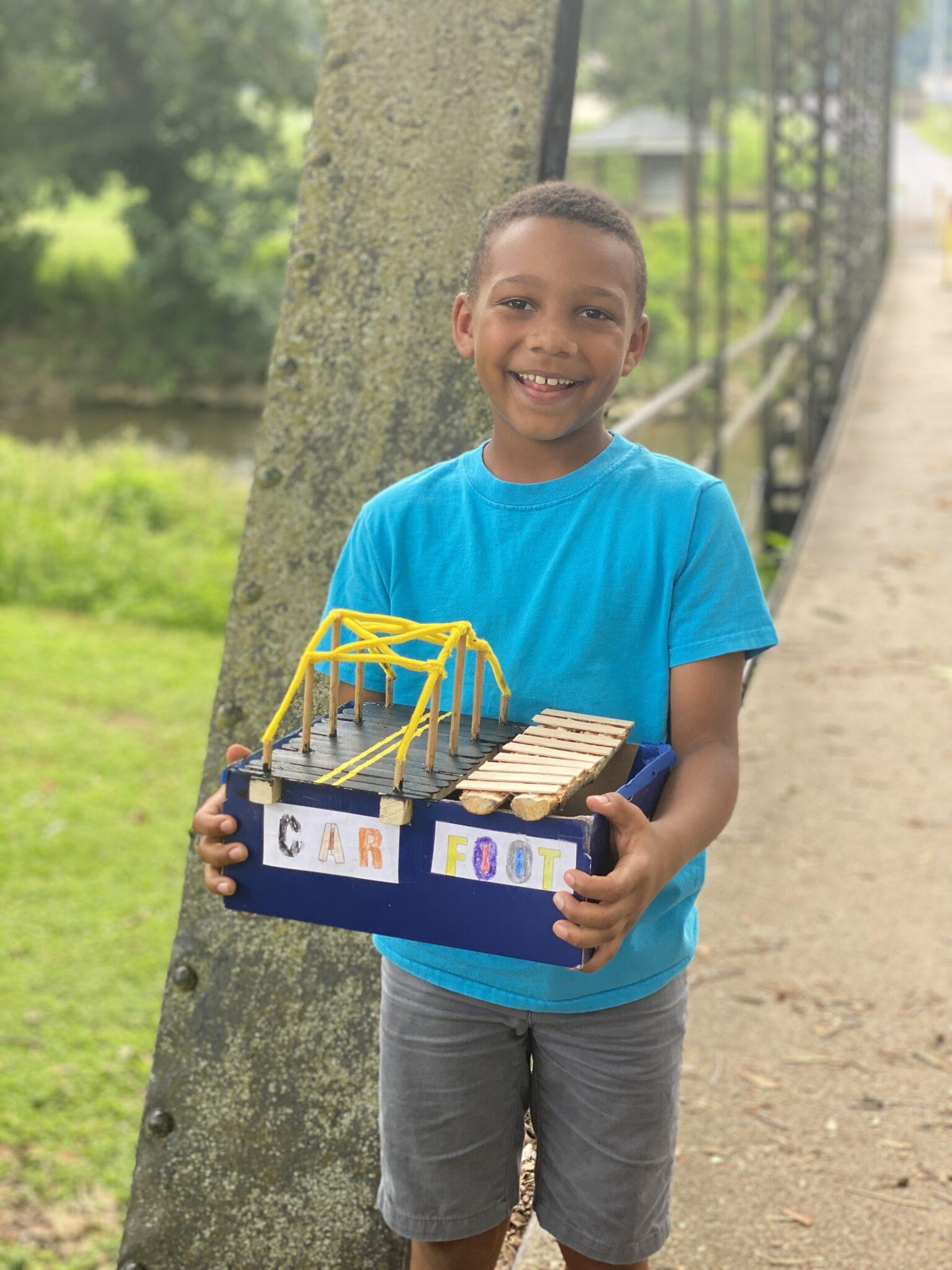 student outside holds bridge art creation