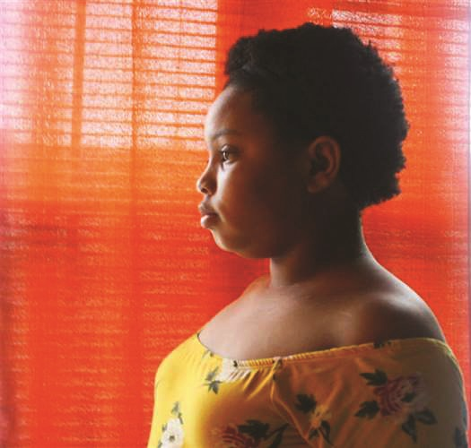 photograph of person looking out window